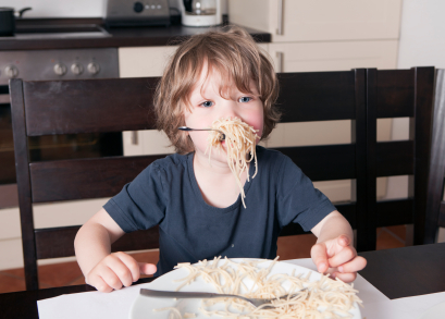 Boy has mouth full of pasta in kitchen